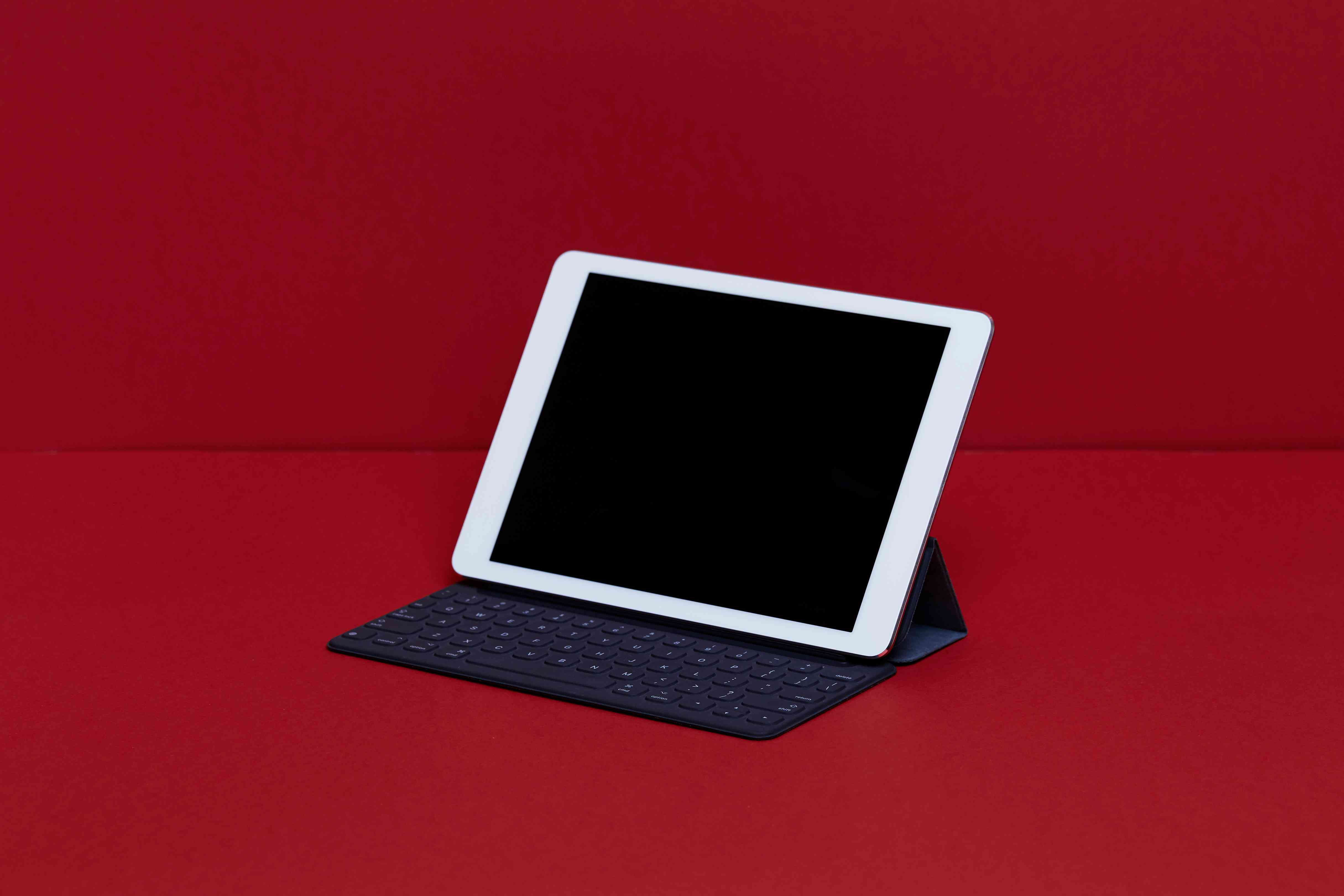 Close-Up Of Digital Tablet With Keyboard On Red Table