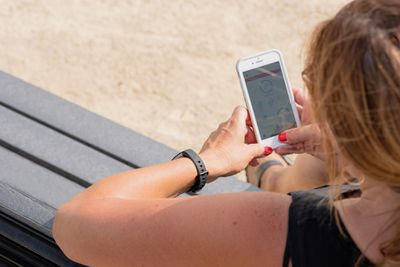 Woman sitting outside on park bench checking Fitbit and smartphone goal stats