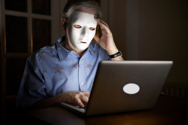 A man wearing a mask while using a computer