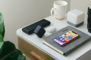 And iPhone on top of a diary on a bedside table with different charging blocks nearby.