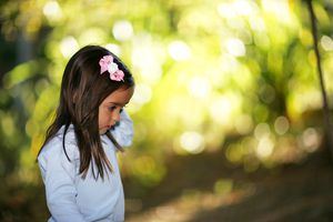 Young girl with flower in hair from the side with a blurry background