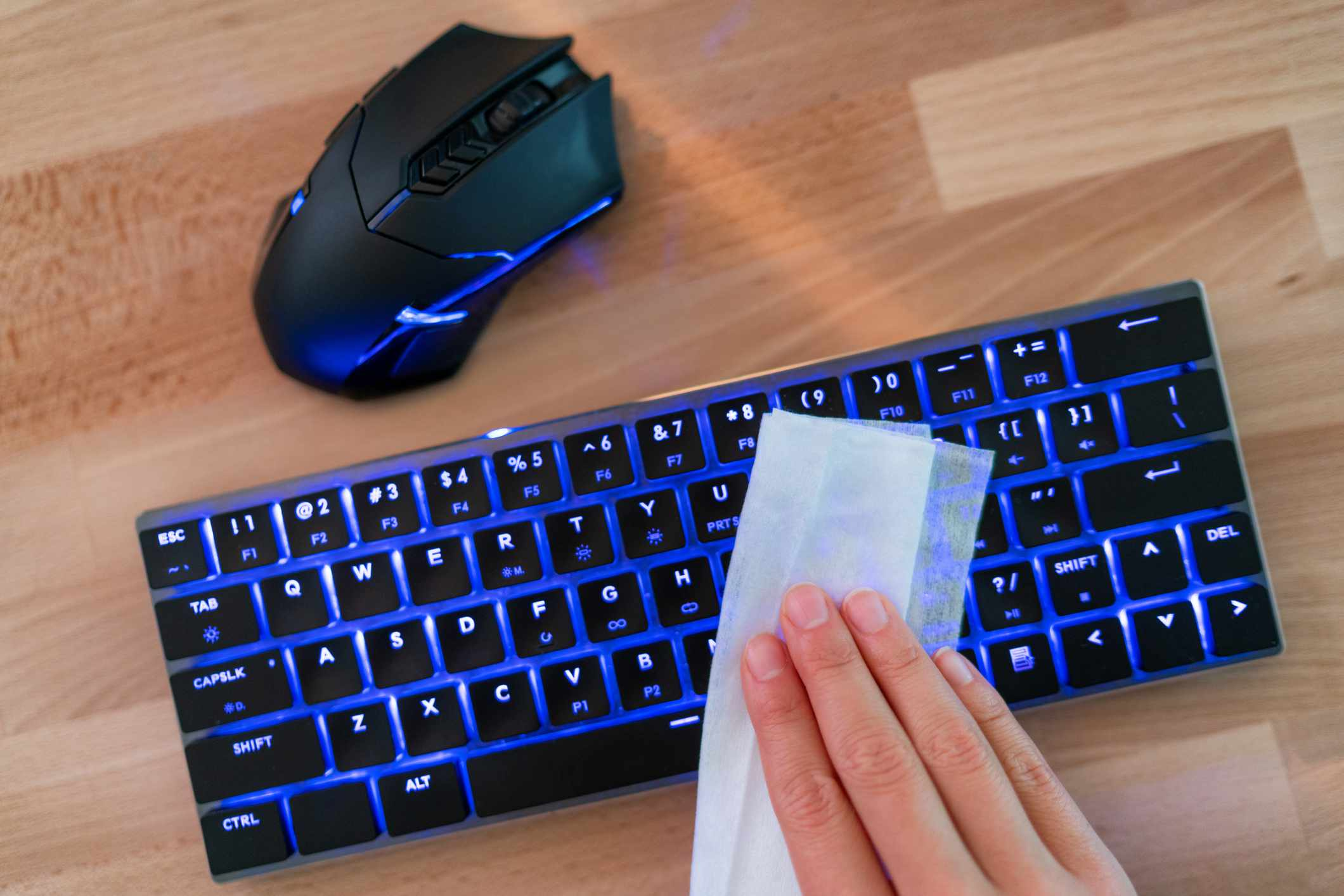 Person wiping a backlit keyboard with a disinfecting wipeh