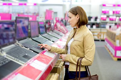 Woman looking at laptops in retail computer store