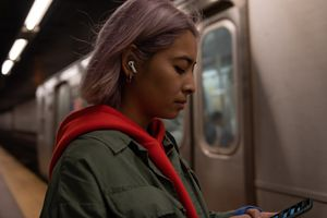 A woman using AirPods Pro on the subway
