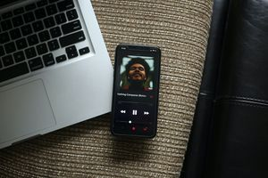 Phone with music player open on corner of Macbook