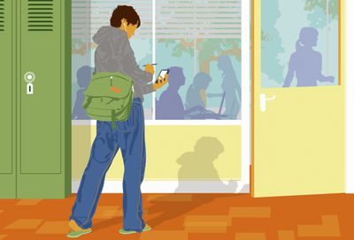 Student with earphones checking cell phone outside classroom