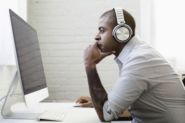 Businessman listening to headphones and working at desk
