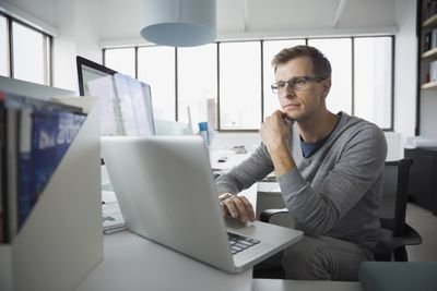 Network administrator using alaptop in an office with other computers