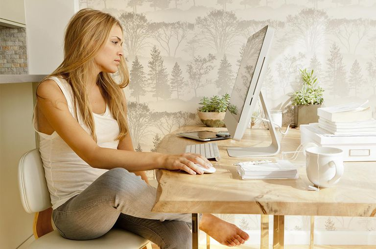 Woman using computer and drinking tea