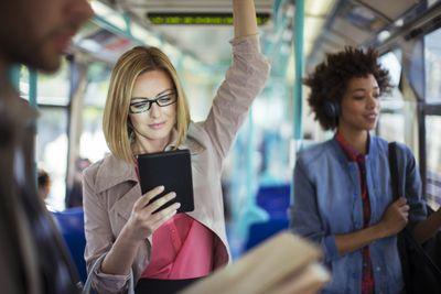 Businesswoman using digital tablet on train