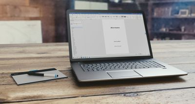 An open laptop on a wooden table displaying a document in Microsoft Word.