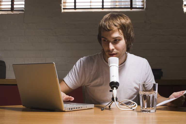 Young man creating a podcast sitting at a laptop with a microphone.