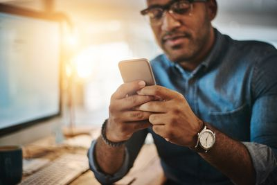 Man looking at his iPhone with a computer in the background
