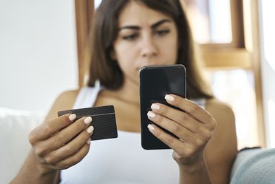Woman Looking at Business Card and Phone