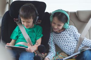 Kid playing game on tablet in car while sister watches