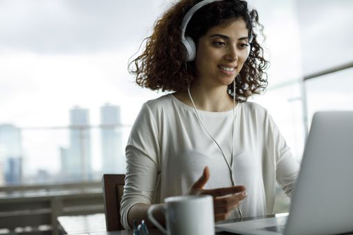 Young woman working at a laptop wearing headphones.