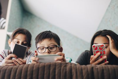 A photo of three kids on a bed, all using smartphones