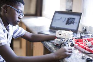 Schoolboy with laptop in robotics class