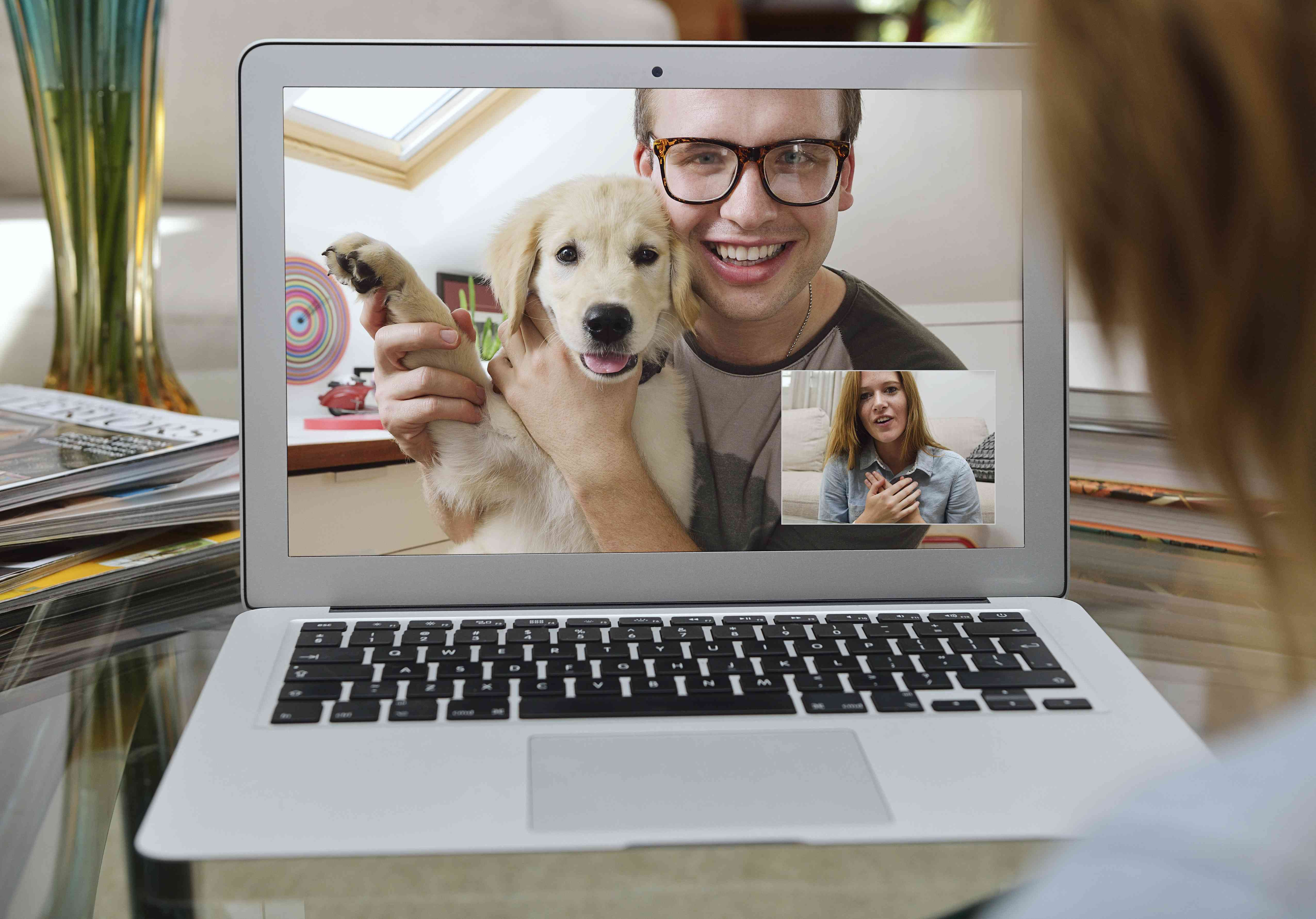 Pet owner showing off a new puppy over Skype on computer