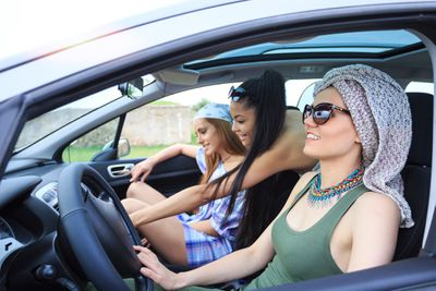 Three friends riding in a car listening to the car stereo