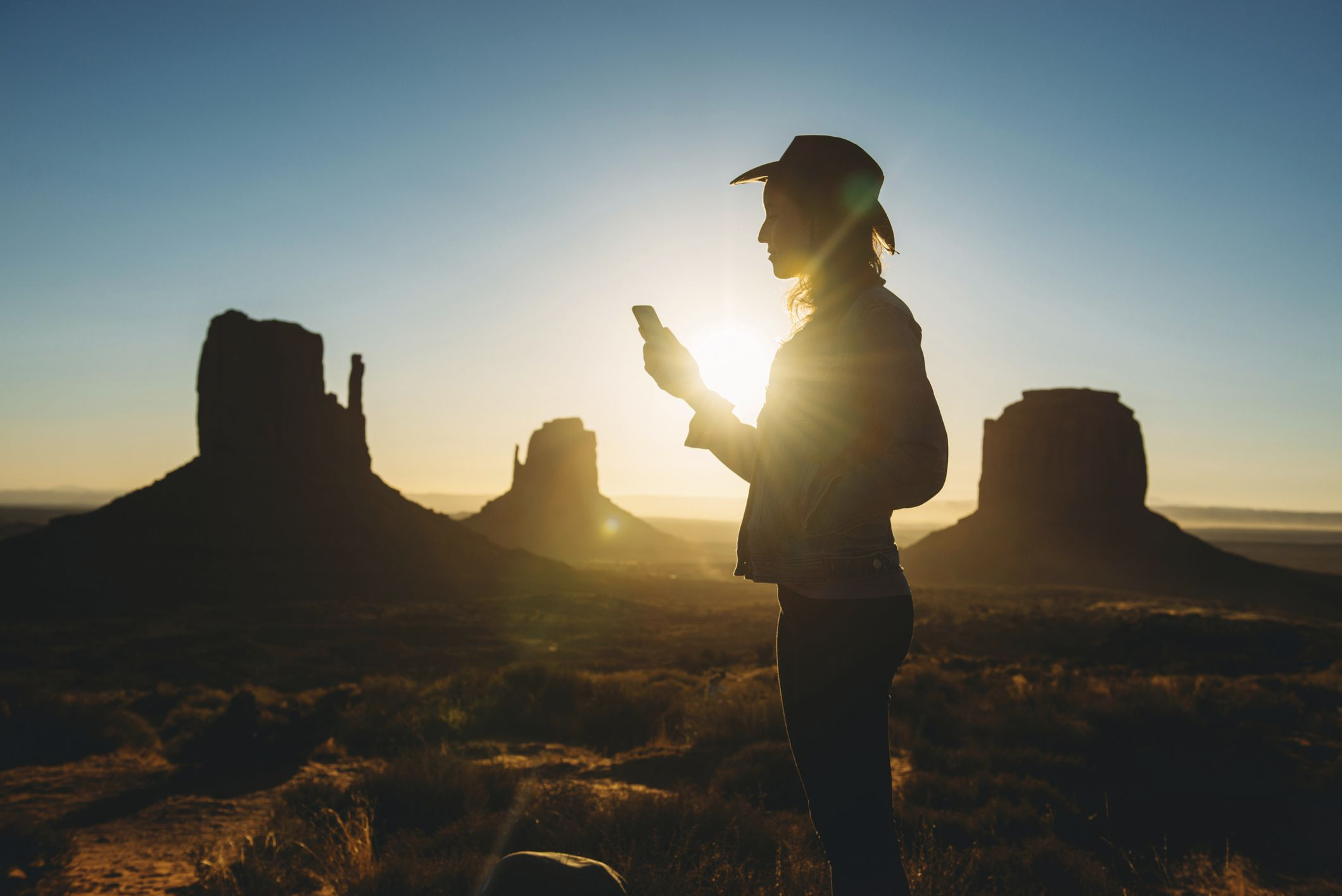 Woman using mobile at sunrise in Monument Valley