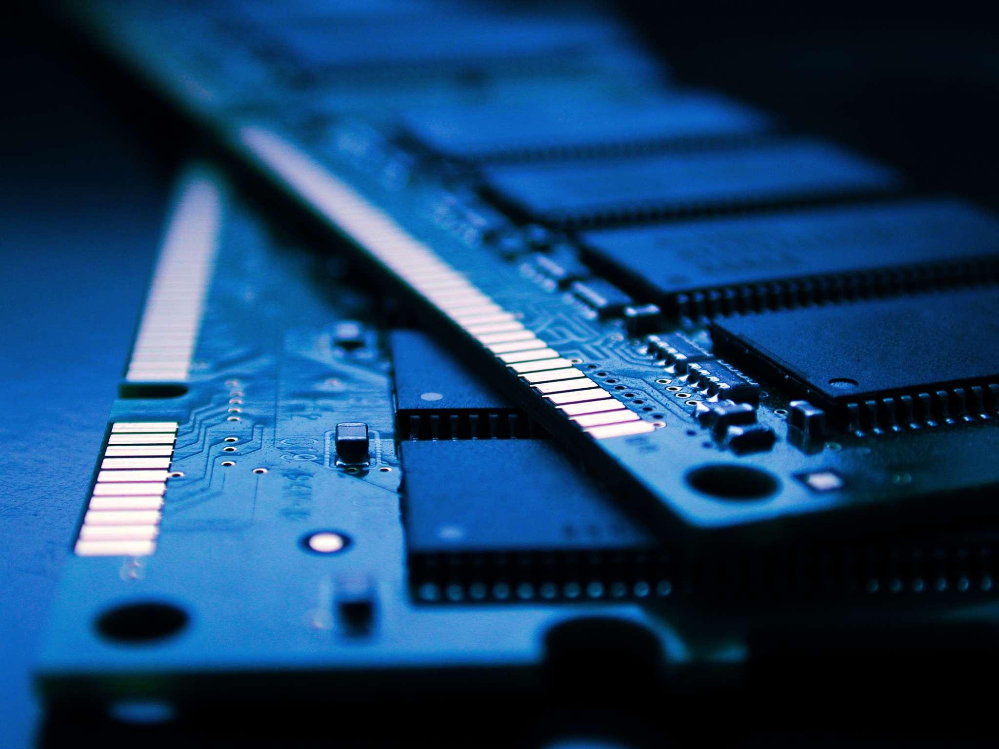 A closeup of two sticks of computer RAM under a soft blue light