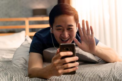 Man on video call on phone while lying in bed