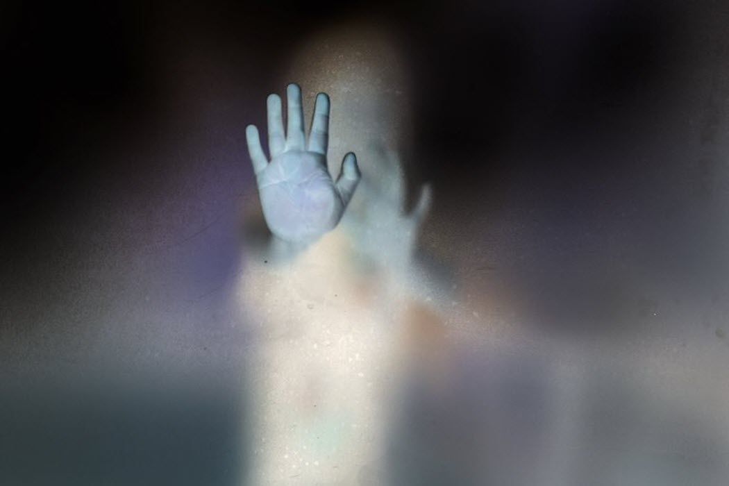 A person trapped behind opaque glass.