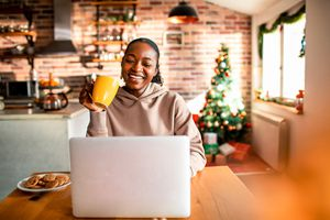 A woman sitting at her desk in a kitchen smiling at her laptop