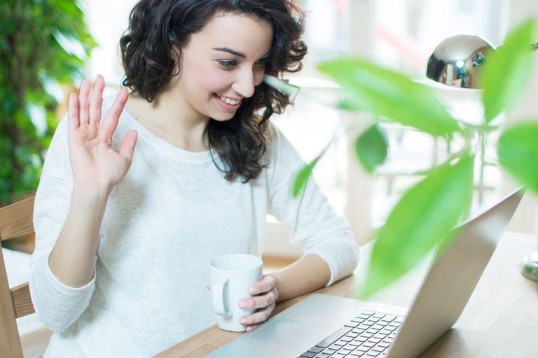 Woman waving to laptop webcam
