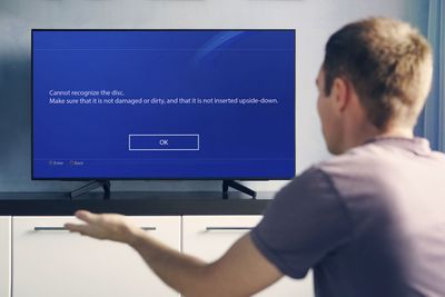 A frustrated man views a PS4 disc ejecting error on his TV.