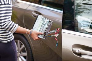 Woman holding head unit without a wiring harness next to an open car door
