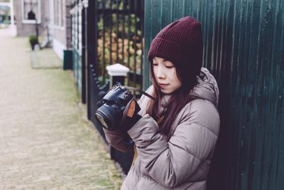 Young woman taking picture on street