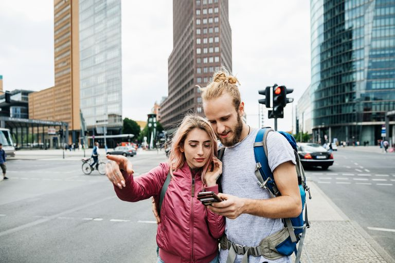 Couple looking at phone for navigation pointing in a city