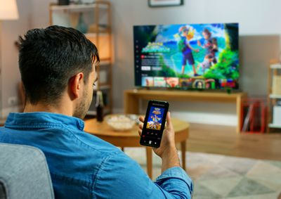 A man in a blue shirt sitting on a lounge and casting a Netflix show from his smartphone to his TV.
