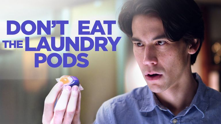 Still image of man holding tide pod with words don't eat the laundry pod
