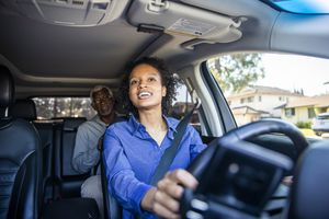 Young woman uber driver smiles at backseat passenger, a man who is using Uber Ride Pass