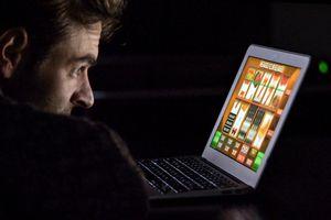 A man playing a slot machine game on a laptop
