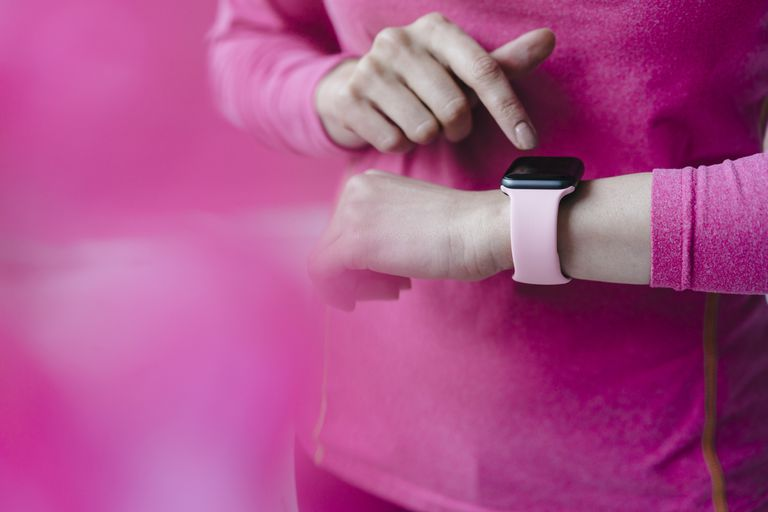 Close-up of woman in pink sportswear adjusting her smartwatch