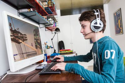 A teenager at a computer playing video games