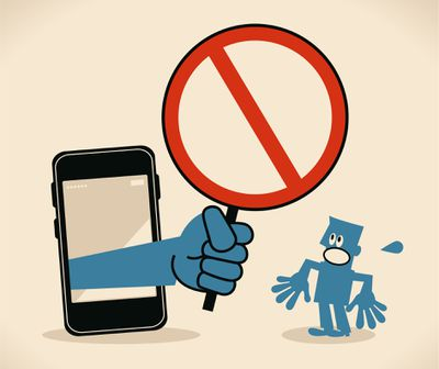 Business person standing in front of a big smart phone, a big hand from the mobile phone holding an empty prohibition sign