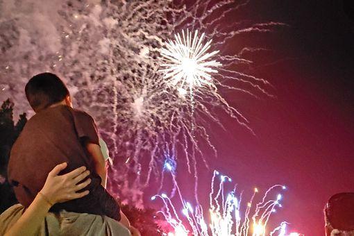 A little boy on daddies shoulders enjoying a fireworks show.