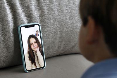 Boy using smartphone as webcam