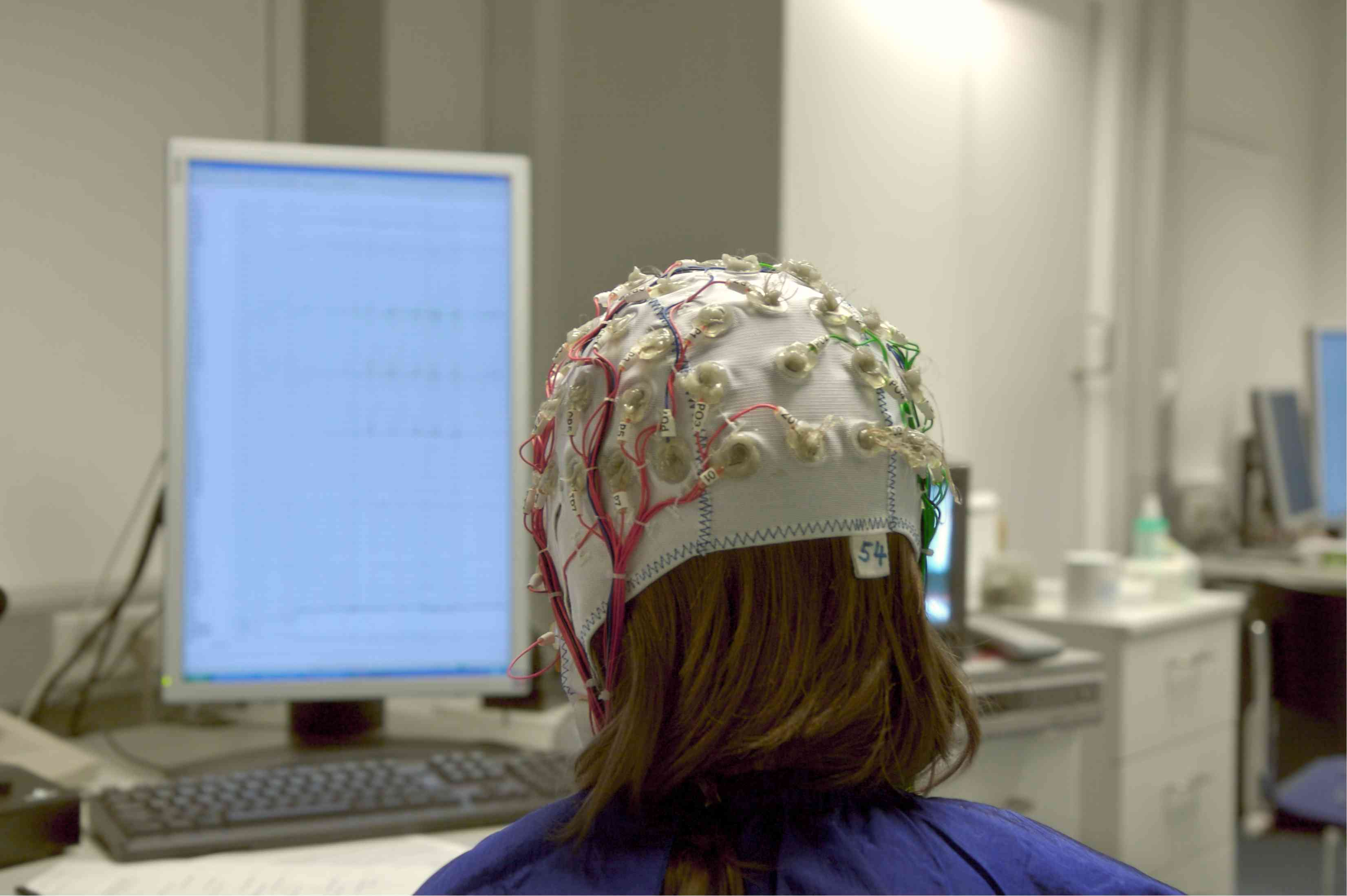 The view from behind of someone connected to an EEG machine sitting in front a computer screen.