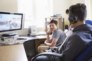 Two boys sitting at a computer desk playing games online