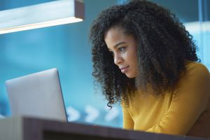 A woman is looking intently at her laptop computer.