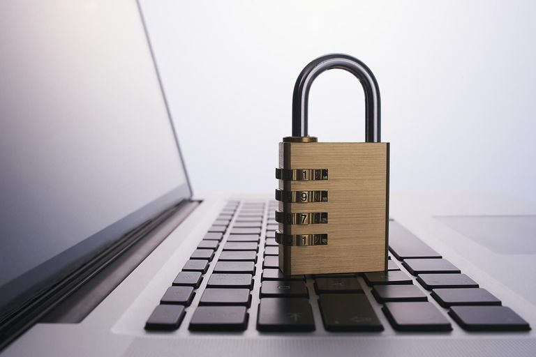 Cyber Security represented by a padlock sitting on the keyboard of a laptop computer