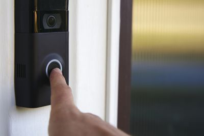 A finger pushing a video doorbell.
