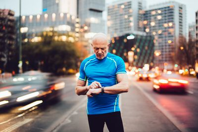 A man standing in a street looking at his smartwatch with traffic behind him