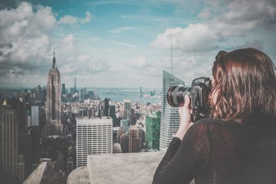 Woman shooting a photo on a rooftop